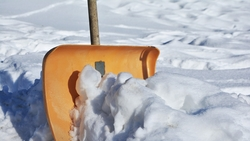 Snow shovel upright in snow bank.