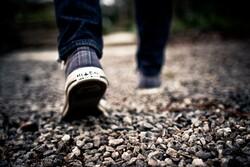 Sneakered feet on gravel.