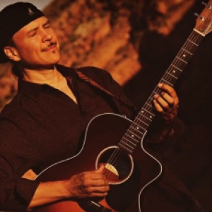 Wade Fernandez playing his guitar at the Canyon de Chelley in Arizona