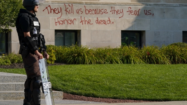 Police in riot gear stand outside the Kenosha County Court House Monday