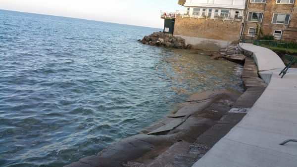 This summer, the high waters of Lake Michigan submerged the Juneway Terrace Beach in Chicago. Residents of an adjacent apartment building say they feel it is at risk. The beach sidewalk was also smashed, and barriers surround a sinkhole.