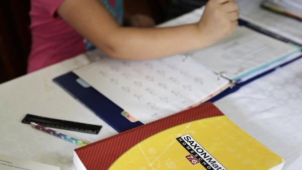 a homeschool math textbook rests on the table where Mabry Grant, 8, works on a lesson with her mom, Donya Grant