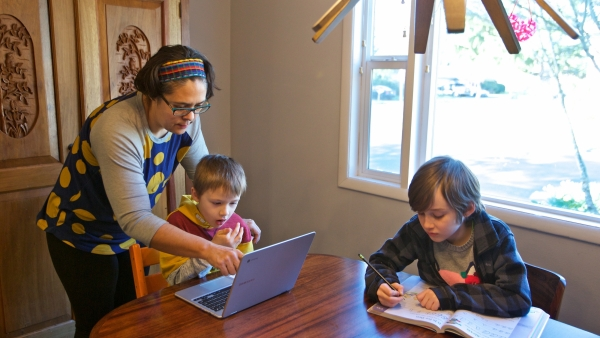 Woman helps her sons with online lessons