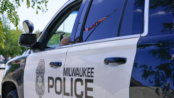 A flag is reflected in the window of a Milwaukee Police Department vehicle