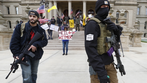 protesters carry rifles near the steps of the Michigan State Capitol building