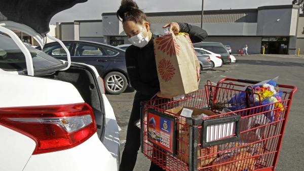 In this July 1, 2020, file photo, Instacart worker Saori Okawa loads groceries into her car