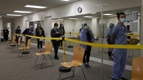 health care workers wait in line to receive the Pfizer-BioNTech COVID-19 vaccine