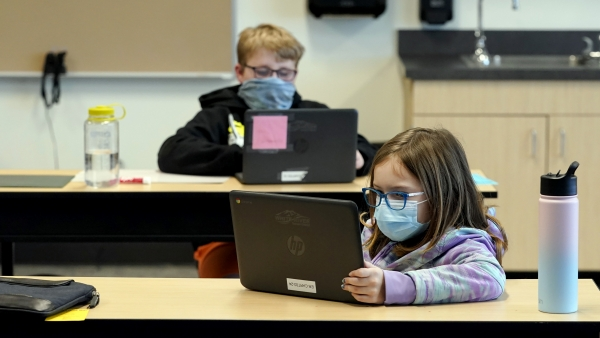 Students wear masks as they work in a fourth-grade classroom.