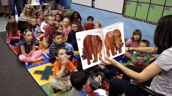 In this Sept. 8 2015, file photo, kindergarten students listen to teacher Amy Holland read