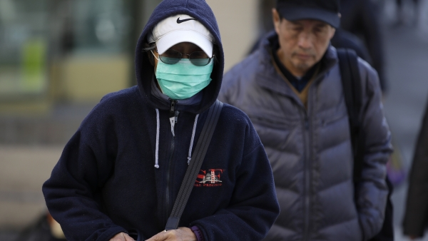 A woman wearing a green surgical mask , blue hoodie and baseball cap walks down the street.