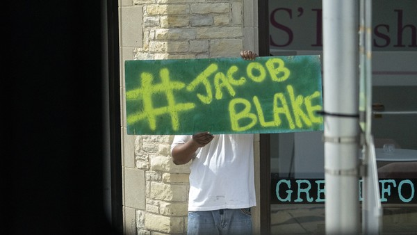 """A person holds up a sign that reads """"#Jacob Blake"""" as the motorcade with Democratic presidential candidate former Vice President Joe Biden aboard passes"""