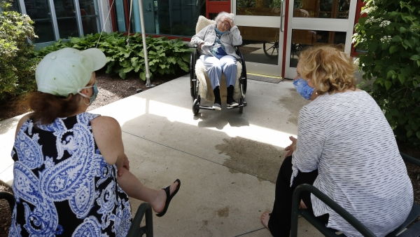 Eva Davis peaks with her daughters at a nursing home
