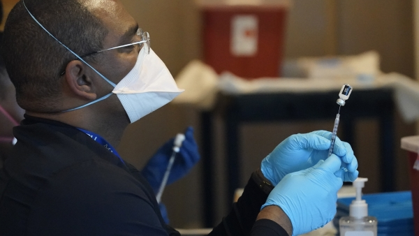 A health care worker fills a syringe