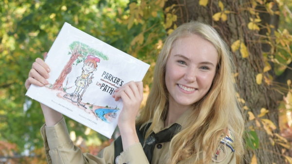 Ava Van Straten poses with the children's book she wrote for her Eagle Scout project