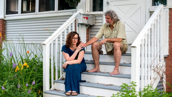 Mariah Clark sits on her porch with her partner
