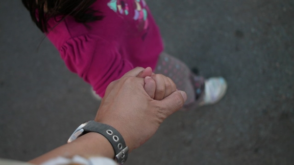 adult walking hand in hand with a young child