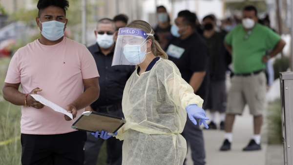 People line up behind a health care worker at a mobile Coronavirus testing site
