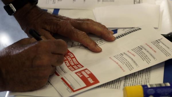 Hand fills out a ballot