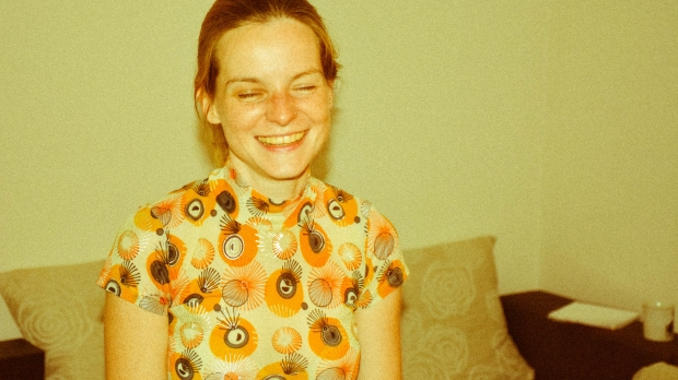 A girl laughs with her eyes closed while wearing an orange, printed short sleeve dress.