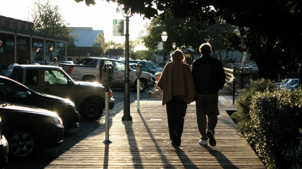 an elderly couple walking side by side on a boardwalk