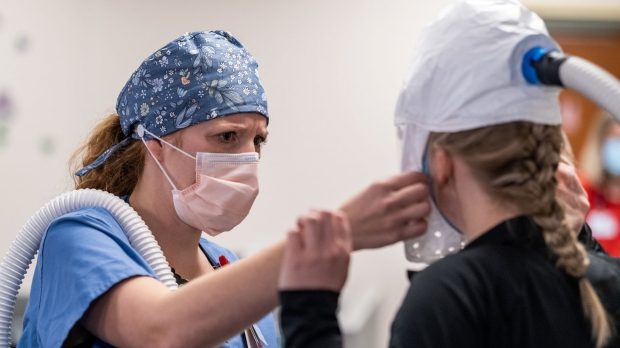 A healthcare worker helps a colleagueadjust her personal protective equipment