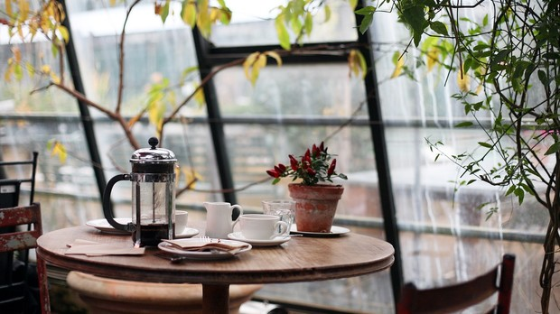 A café table with coffee and cups on table in front of large windowed wall.