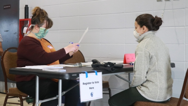 A poll worker helps a voter register