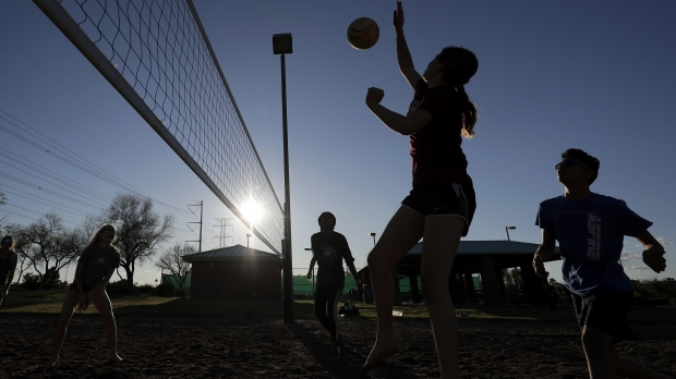 Friends gather to play volleyball at a local park during the coronavirus pandemic