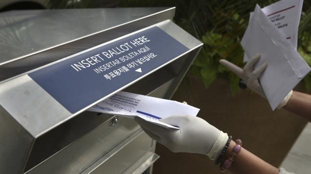 A woman drops off a mail-in ballot at a drop box