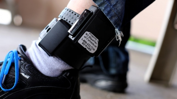 registered sex offender shows his GPS ankle monitoring equipment