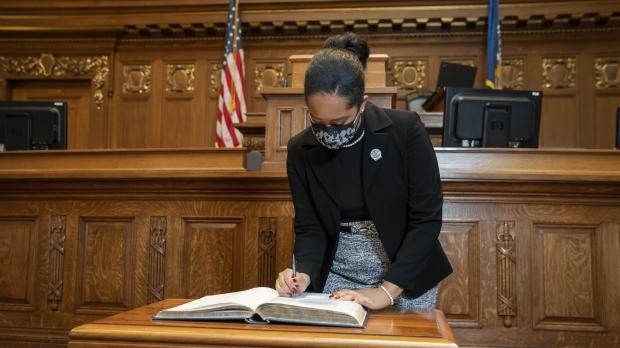 Rep. Dora Drake signing registration book at inauguration