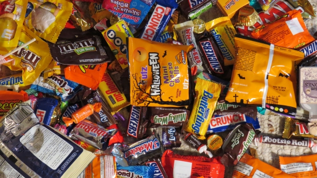 A variety of hand-out sized candy is laid out flat on display.