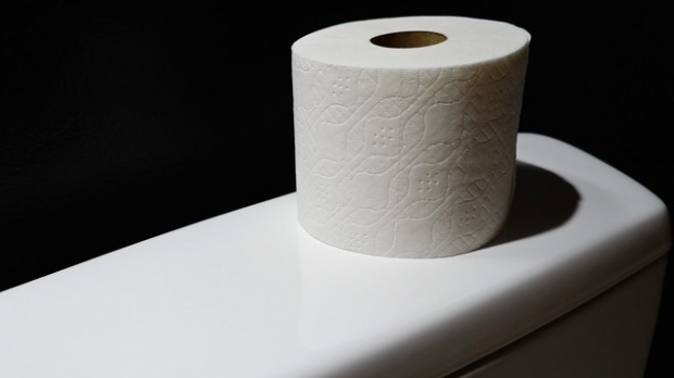 toilet paper on the back of a toilet