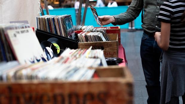 man standing in front of vinyl records