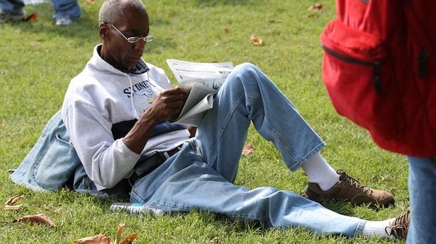 Black man reading newspaper on the lawn