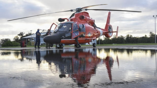 Coast Guard members inspect a helicopter