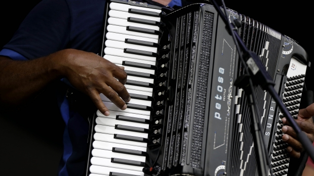 A person plays the accordion on a stage.