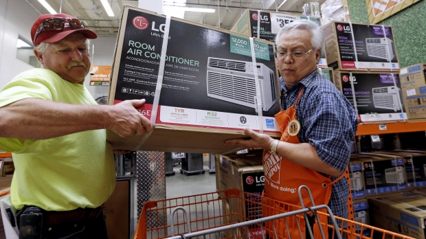 A Home Depot worker assists customer in lifting new air conditioning unit in shopping cart