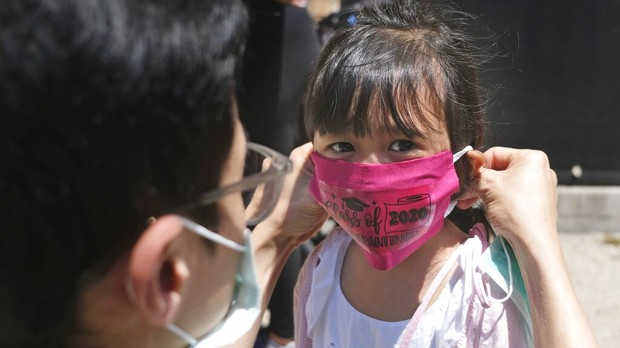 A parent placing a cloth face mask on the face of their child.