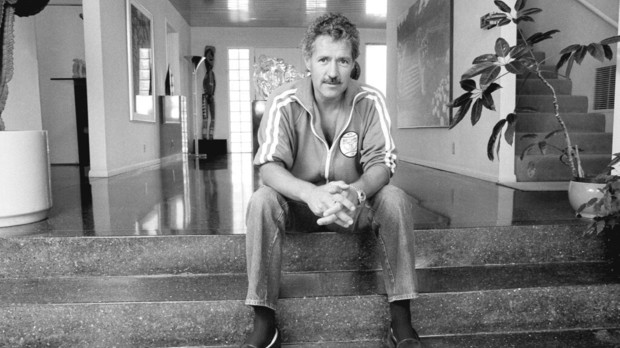 A black and white image of Alex sitting on some steps inside his home.