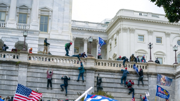 A view of the side of the capitol building where several people are clinging to the side and climbing.
