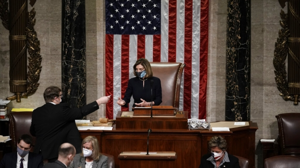 Nancy Pelosi sits behind a giant desk in front of a large American flag.