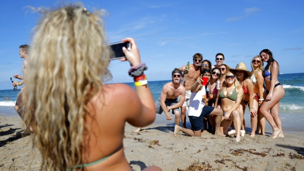 A group of students gather for a photo on the beach and in the foreground we see one student squatting with a cellphone to snap the shot.