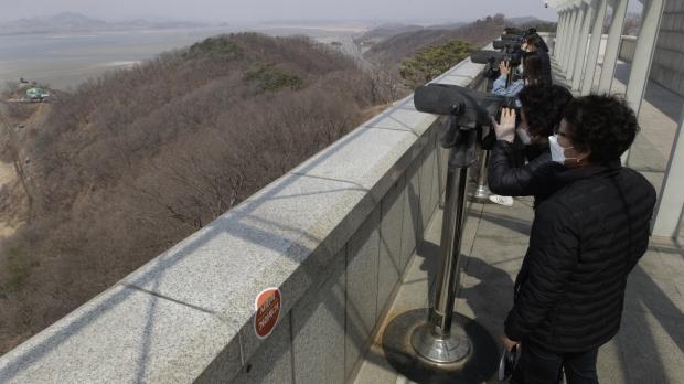 Person gazing through telescope at North Korea