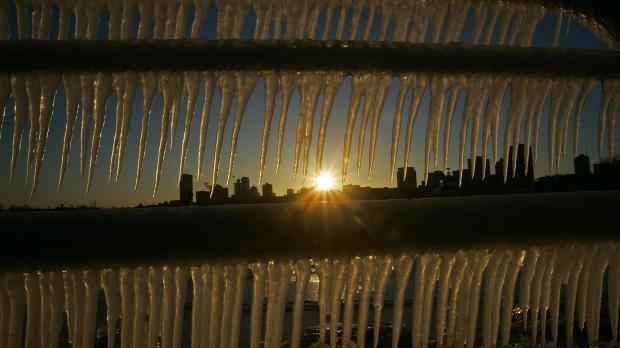 The sun sets on a sub zero day behind the skyline of Milwaukee