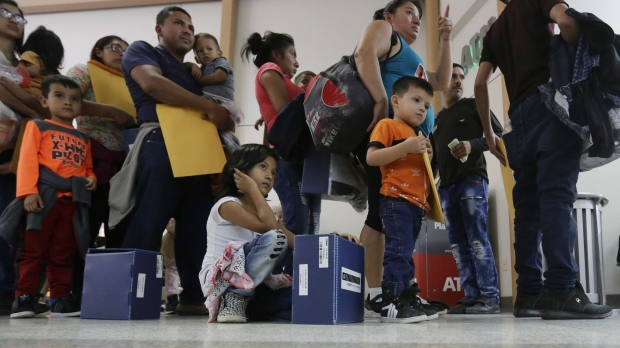 Immigrant families wait for bus after processing in Texas