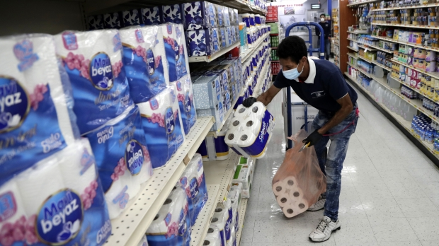 Man stocks store shelves with toilet paper