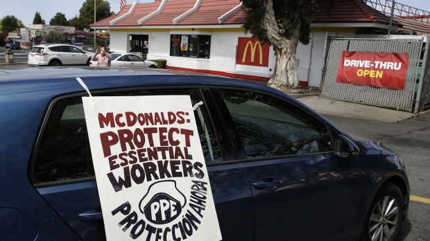 There is a car with an artistic sign asking Mcdonald's to protect essential workers by providing PPE in front of a McDonald's location.