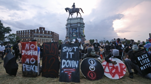 Protesters with shields and gas masks wait for police action as they surround the statue of Confederate Gen. Robert E. Lee in Richmond, Virginia.