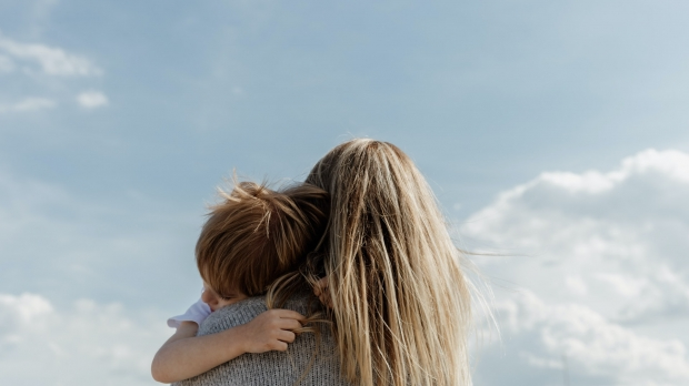 A woman holds and hugs a child.